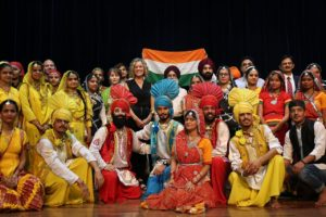 Katherine in Western clothes among people in traditional Indian dress and the flag of India